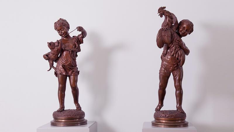 Скульптуры «Девочка, играющая скошкой» и «Мальчик спетухом»
